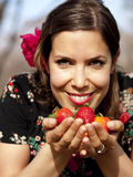 Schönes Mädchen, das im Frühjahr frische Erdbeeren riecht Lizenzfreies Stockbild