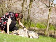 Schönes Mädchen, das im Frühjahr ihren Hund während eines Wegs streichelt stockfotos