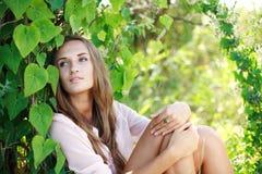 Schönes Mädchen, das im Garten sich entspannt Stockfotografie
