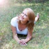 Schönes Mädchen, das im Gras whith Blendenfleckeffekt liegt Stockfotografie