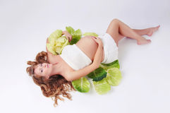 Schönes schwangeres Mädchen, das im Kohl liegt Lizenzfreie Stockfotos