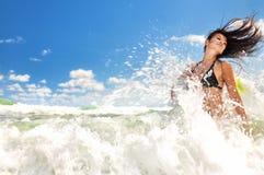 Schönes Mädchen, das im Ozean spritzt Stockfotografie