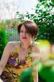 Schönes Mädchen, das im Park auf Hintergrundgrün lächelt Stockfotos