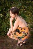 Schönes Mädchen, das im Park auf Hintergrundgrün lächelt Stockbilder