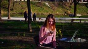 Schönes Mädchen, das im Park mit Laptop sitzt und durch Smartphone spricht stock video