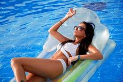 Schönes Mädchen, das im Pool auf einer aufblasbaren Matratze ein Sonnenbad nimmt lizenzfreie stockfotos