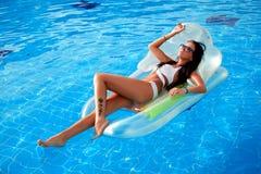 Schönes Mädchen, das im Pool auf einer aufblasbaren Matratze ein Sonnenbad nimmt stockfotos