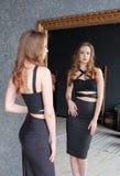 Schönes Mädchen, das im Spiegel schaut und auf einem eleganten Kleid - Porträt einer jungen Frau in einer Umkleidekabine versucht Stockfotos