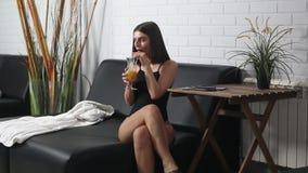 Schönes Mädchen, das Juice On ein Ruhesessel trinkt stock footage