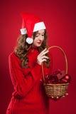 Schönes Mädchen, das Korb mit Weihnachtsbaumdekorationen hält Stockbild