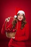 Schönes Mädchen, das Korb mit Weihnachtsbaumdekorationen hält Lizenzfreie Stockbilder