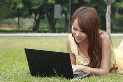 Schönes Mädchen, das Laptop auf Gras verwendet Lizenzfreie Stockfotos