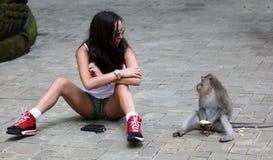 Schönes Mädchen, das mit Affen am Affewald in Bali Indonesien, hübsche Frau mit wildem Tier spielt Stockfotografie