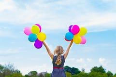 Schönes Mädchen, das mit bunten Ballonen am Sommertag gegen den blauen Himmel spielt Lizenzfreies Stockbild