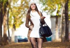 Schönes Mädchen, das mit Handy im Herbst geht Stockfoto