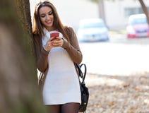 Schönes Mädchen, das mit Handy im Herbst plaudert Stockbilder