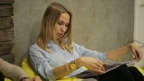 Schönes Mädchen, das mit ihrem Freund spricht und eine Zeitschrift liest stock video footage