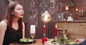 Schönes Mädchen, das mit ihrem Freund spricht, während der Kellner Champagner gießt stock footage