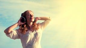 Schönes Mädchen, das Musik auf Kopfhörern hört lizenzfreie stockfotos