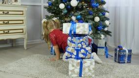 Schönes Mädchen, das nach Geschenken unter dem Weihnachtsbaum sucht stock footage