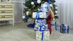 Schönes Mädchen, das nach Geschenken unter dem Weihnachtsbaum sucht Stockfotos