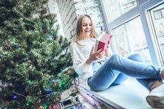 Schönes Mädchen, das nahe Baum des neuen Jahres mit Geschenk sitzt lizenzfreie stockfotografie