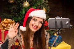Schönes Mädchen, das nahe Baum des neuen Jahres sitzt und selfies macht Lizenzfreies Stockbild