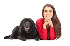 Schönes Mädchen, das nahe bei ihrem Schoßhund liegt Stockfotografie
