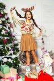 Schönes Mädchen, das nahe dem Weihnachtsbaum steht Lizenzfreies Stockfoto