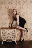 Schönes Mädchen, das nahe dem Weinlese nightstand aufwirft Stockbilder