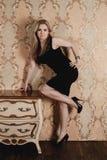 Schönes Mädchen, das nahe dem Weinlese nightstand aufwirft Stockbild
