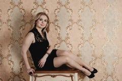 Schönes Mädchen, das nahe dem Weinlese nightstand aufwirft Stockfotografie