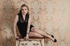 Schönes Mädchen, das nahe dem Weinlese nightstand aufwirft Stockfotos