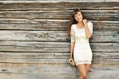 Schönes Mädchen, das nahe einer Wand steht und zu Ihnen lächelt Lizenzfreie Stockfotos