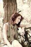Schönes Mädchen, das nahe Fahrrad sitzt. Lizenzfreies Stockbild