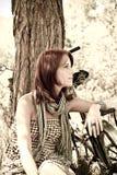Schönes Mädchen, das nahe Fahrrad sitzt. Lizenzfreie Stockbilder