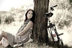 Schönes Mädchen, das nahe Fahrrad sitzt. Stockfotos