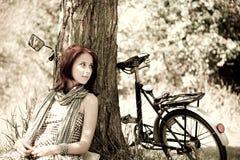 Schönes Mädchen, das nahe Fahrrad sitzt. Foto in Retro- s Stockbilder