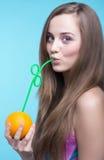 Schönes Mädchen, das Orangensaft durch ein Stroh trinkt Stockbilder