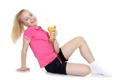 Schönes Mädchen, das Orangensaft trinkt Stockfotografie