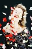 Schönes Mädchen, das in rosafarbene Blumenblätter legt Lizenzfreies Stockbild