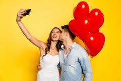 Schönes Mädchen, das selfie während ihr Freund küsst sie nimmt stockbilder
