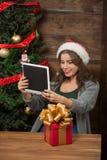 Schönes Mädchen, das selfies auf Tablet-PC nahe Baum des neuen Jahres macht Stockfotografie