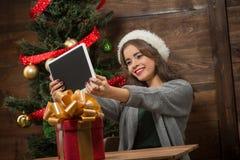 Schönes Mädchen, das selfies auf Tablet-PC nahe Baum des neuen Jahres macht Lizenzfreie Stockfotos