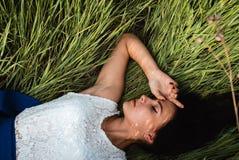 Schönes Mädchen, das sich am Gras hinlegt stockbild