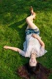 Schönes Mädchen, das sich am Gras hinlegt Lizenzfreie Stockfotos