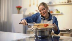 Schönes Mädchen, das Soße bei der Unterhaltung am Telefon, einladende Freunde für Abendessen kocht stock video footage