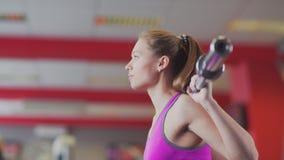 Schönes Mädchen, das Sport spielt und Übungen mit einem Barbell tut stock video