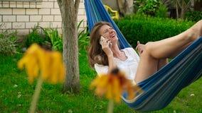 Schönes Mädchen, das am Telefon beim Lügen in einer Hängematte spricht stock footage