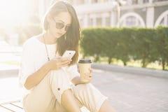 Schönes Mädchen, das Telefon beim Sitzen mit Tasse Kaffee verwendet lizenzfreie stockfotografie